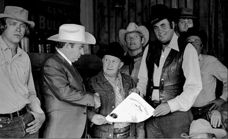 "(L-R) Bill Wright, cartoonist Max Harrison, Tex Barr, Leonard Worth, Sunset Carson, Bill Riley and Jesse Baker during the making of ""Marshal of Windy Hollow"". Max is presenting Tex Barr with the Kentucky Colonel certificate."