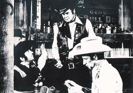 "Sunset Carson holds a gun on Glenn Huffman (L) and Leonard Mann (R) in the saloon from ""Marshal of Windy Hollow""."