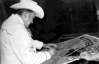 "Tex Ritter signs one of his movie posters for a fan during the filming of ""Marshal of Windy Hollow""."
