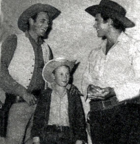 "Two TV western giants and one small fry. James Arness of ""Gunsmoke"" chats with Clint Walker of ""Cheyenne""."