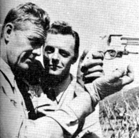 "Examining a pistol in-between scenes of TV's ""Tales of the Texas Rangers"" are stars Willard Parker (Jace Pearson) and Harry Lauter (Clay Morgan). Circa 1959."