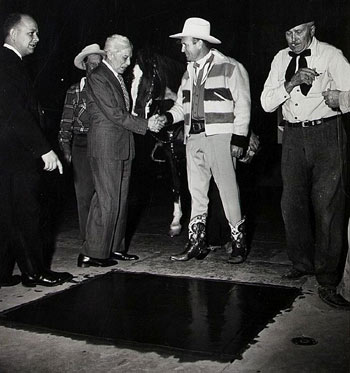Gene Autry is congratulated by Sid Grauman as Gene is about to be inducted into the Walk of Fame in front of Graunman's Chinese Theatre on Dec. 23, 1949. Gene's were the 89th set of hand prints left in the Forecourt of the Stars. (Thanx to Bobby Copeland.)