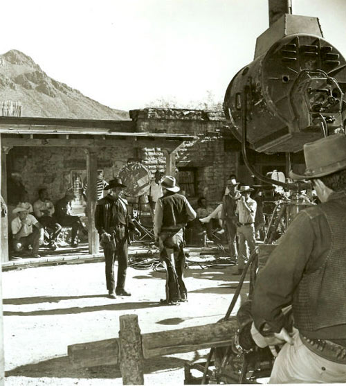 "Cameron Mitchell surrounded by the crew during a scene for ""High Chaparral"". Mark Slade on the right behind the camera. (Courtesy ""High Chaparral"" newsletter. info@highchaparralnewsletter.com)"
