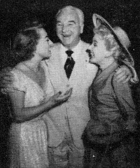 William Boyd gives a hug to actress Joan Crawford and wife Grace Bradley in mid-1951.