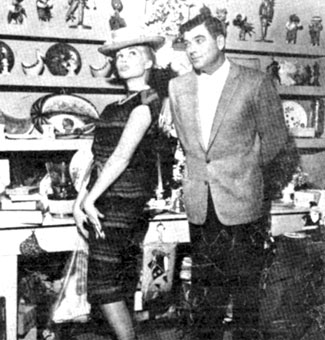 "John Bromfield, star of TV's ""Sheriff of Cochise"" and ""U. S. Marshal"" watches wife Larri Thomas try on a funny hat in a Mexican curio store in 1959."