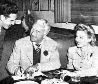 Bill Boyd and wife Grace Bradley sign an autograph for a fan while dining at the popular Brown Derby restaurant in L.A.