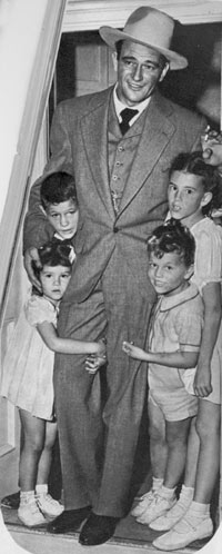 John Wayne in late 1944 with his children, Michael and Pat and the girls Toni and Melinda.