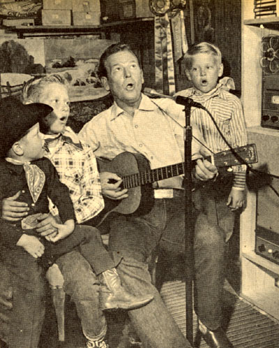 Rex Allen's sons Mark, Chico (Rex Jr.) and Curtis harmonize with dad as Rex records a song on a tape recorder.