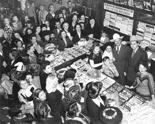 A crowd gathered at Dottie's Music Department in McCrory's Department Store on Texas Street in Shreveport, LA, in 1948 to greet Gene Autry and Johnny Bond. (Photo courtesy Edmond Smith of Little Rock, AR, seen standing with Gene.)
