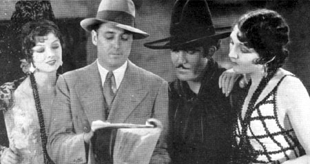 "Director Spencer Bennet goes over the script for ""Rogue of the Rio Grande"" ('30 World Wide) with Myrna Loy, Jose Bohr and Carmelita Geraghty. This was Bennet's first talkie."