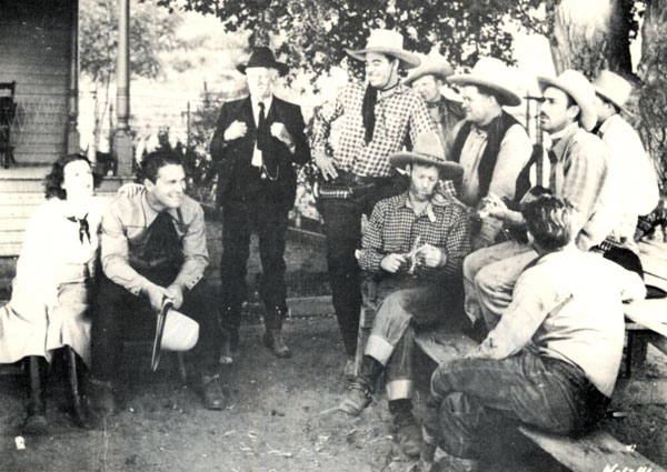 "Taking a break from making ""Law of .45s"" ('35 First Division) are (l-r) Molly O'Day, Big Boy Williams, Lafe McKee, Glenn Strange, Jack Evans, Jack Kirk, Sherry Tansey, unknown behind Tansey, Al St. John seated, unknown."