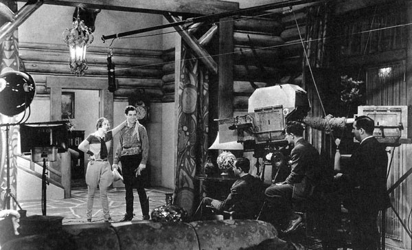 "Joan Crawford and Johnny Mack Brown on the set for MGM's ""Montana Moon"" ('30). Producer/director Malcolm St. Clair is seated by the camera. (Thanx to Jerry Whittington.)"