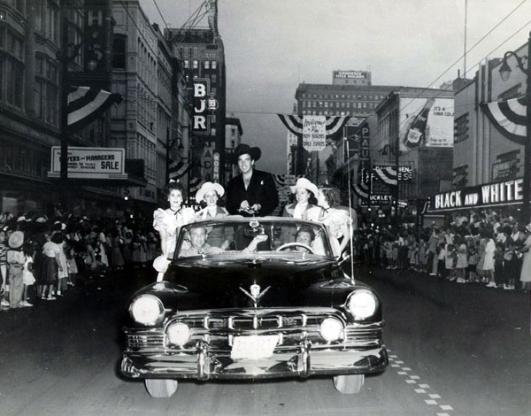 Lash LaRue and a bevy of cowgirls ride in a Paterson, NJ, parade. Date unknown but note the Welcome to Roy Rogers, Dale Evans banner in the background. (Thanx to Jerry Whittington.)