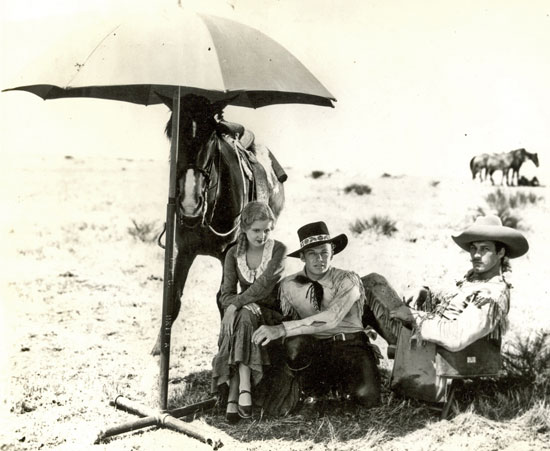 "Getting out of the sun, Lucile Browne, Rex Bell and Tom Tyler wait for the next scene of ""Battling with Buffalo Bill"" ('31 Universal serial)."
