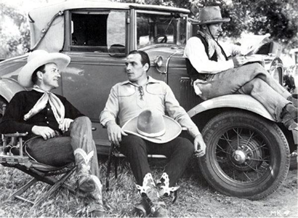 "Jack Perrin and Tom Tyler chat during a break from filming ""Mystery Ranch"" ('34 Reliable) while character player Jimmy Aubrey catches up on the news. For whatever reason Perrin was billed Jack Gable in this film."