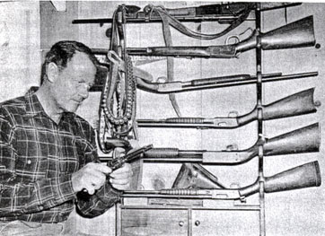 Joel McCrea looks over his ranchhouse gun rack.