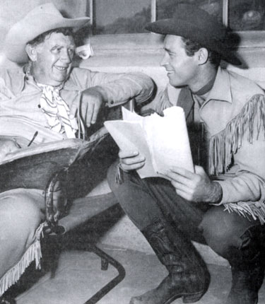 "Andy Devine and Guy Madison check over their scripts for the next episode of ""Wild Bill Hickok""."