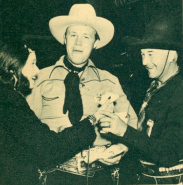 "There's snacks all around for Rosemary Lane (?), Wayne Morris and William Boyd as Hopalong Cassidy at the premiere of Warner Bros. ""Virginia City"" in early 1940 in Reno, NV."