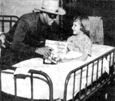Clayton Moore talks with a crippled child and presents her with a Lone Ranger record at the New Orleans Charity Hospital on February 4, 1956.