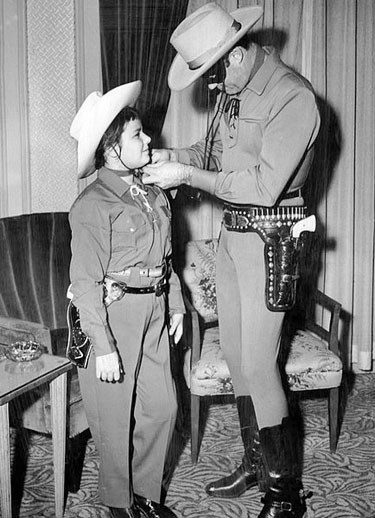 "Clayton Moore ties the scarf of a young Boston fan. Clayton was in Boston to promote ""The Lone Ranger"" 1956 film."