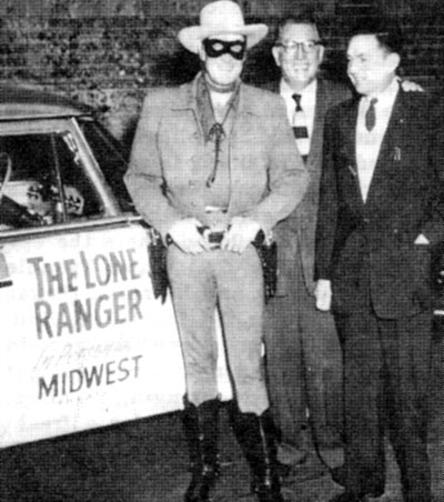 "Clayton Moore is welcomed to Oklahoma City, OK, by Warner Theatre managers while promoting the 1956 ""Lone Ranger"" movie."