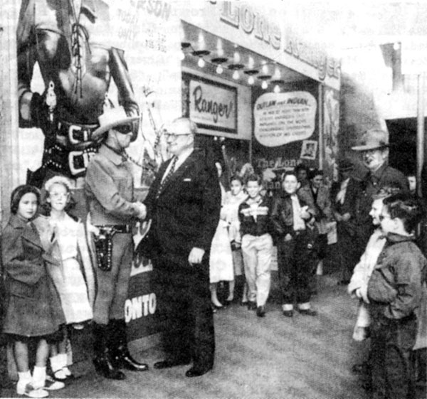 "Clayton Moore is greeted by Ray Jones, manager of the Worth Theatre in Fort Worth, TX, along with a throng of admiring children during the 1956 promotional tour for the theatrical version of ""The Lone Ranger""."