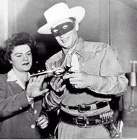 Radio Lone Ranger Brace Beemer shows his pistol to an admirer.