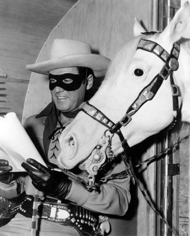 "Clayton Moore studies his script for the big budget 1956 ""Lone Ranger"" movie."