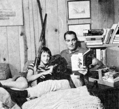 At home, John Russell reads to daughter Renata Amy Russell, age 12. The dog's name is Jezabel. Circa 1959.