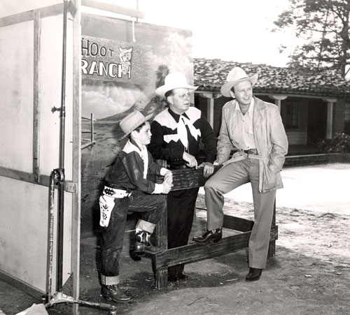 Youngster Steve Salina asks Hoot Gibson questions about old cowboy films which Hoot discusses and shows during a filmed but apparently never released June 1950 TV series. Hoot also had guests drop by such as Rand Brooks pictured here. Hoot did host a series of 15 minute TV programs promoting the sale of Aristo Blue Chinchillas. Music was included by the Jimmie Haskell Trio. That show was aired and I have several of those which appear to have all been filmed at the same time.