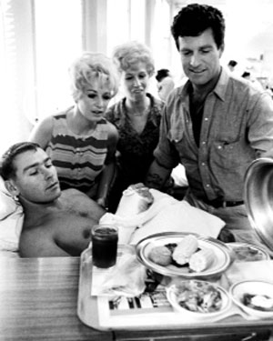 "Hugh O'Brian, TV's ""Wyatt Earp"", unveils dinner in July 1967 for Marine Sgt. William Ferrell, a patient at Yokosuka Naval hospital. He was wounded the previous month at Dong Ha, Viet Nam. Behind them are Linda Michele and Ruth Lawrence of the U.S.O.'s ""Guys and Dolls"" dance troupe."