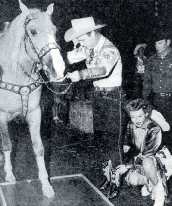 Roy Rogers and Dale Evans assist Trigger in putting his hoofprints in cement at the old Hitching Post theatre in L.A.