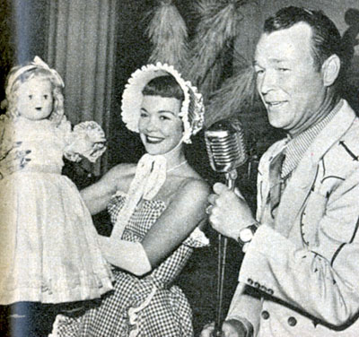 Roy Rogers helps Jane Wyman auction off one of her dolls at the Christmas 1950 Chuck Wagon Whoop De Do at the Beverly Hills Hotel. $30,000 was raised for the building fund of a nursery school for visually handicapped children. The doll sold for $950 to restauranteur Mike Romanoff.