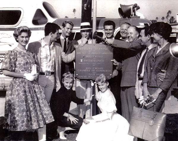 "In 1959 this group of Warner Bros. stars were sent out to plug the movie ""The Young Philadelphians"". None of the group was actually in the movie but they went all across the country in the tour bus seen in the photo. (L-R) Arleen Howell, Peter Brown, Troy Donahue, Will Hutchins, Roger Smith, Alan Hale Jr., the WB exec who was sending them off on the tour, Louis Quinn and Jacqueline Beer. Kneeling are Diane Jergens (married to Peter Brown from '58-'60) and Connie Stevens. (Courtesy Will Hutchins.)"