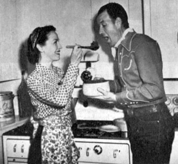 Bill Elliott's wife Helen gives Bill a sample of her stew with vegetables from their own garden. Photo from 1944. They were married from 1927 til a divorce in 1961.