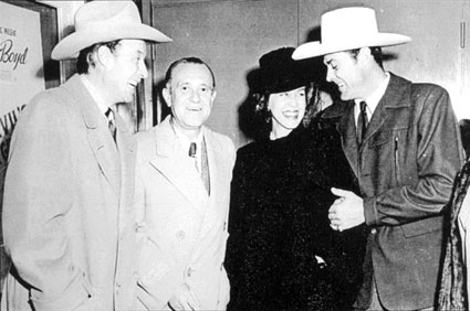 "William Elliott, Republic producer Edward J. White, Mrs. Elliott and Allan Lane at a Hitching Post Theater screening. Note the William Boyd ""Hoppy"" poster on the left."