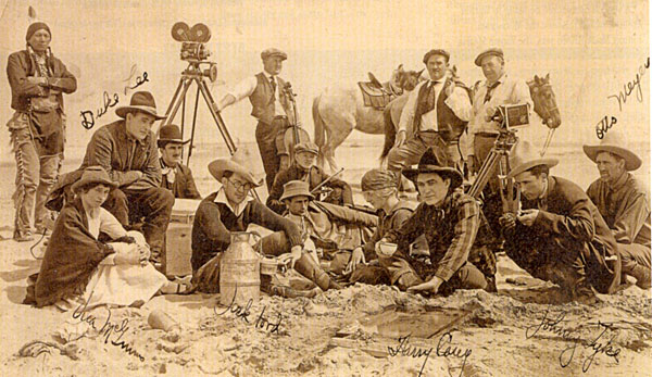 Relaxing between scenes, director John Ford (with glasses), star Harry Carey and players Johnny Tyke, Otto Meyer, Duke Lee and rodeo cowgirl Vera McGinnis. Circa 1917.