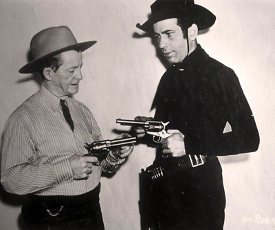 "Is that Lash LaRue? No, it's Humphrey Bogart getting a few pointers on how to handle a six-gun from real life badman Al Jennings in preparation for Bogie's role in ""Oklahoma Kid"" ('39 WB). (Thanx to Bobby Copeland.)"