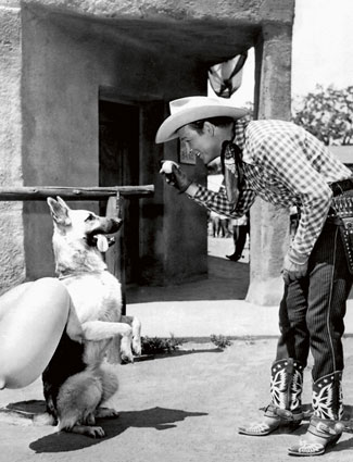 Roy Rogers in a training session with his dog Bullet in 1951. I just can't figure out why the balloons are tied around Bullet's neck.