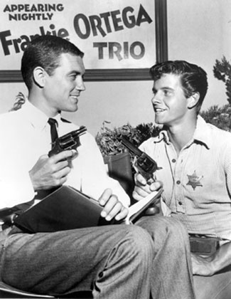 "Peter Brown, Johnny McKay on ""Lawman"", visits the Warner Bros. ""77 Sunset Strip"" set to compare firearms with Roger Smith, Jeff Spencer on that series. (10/30/59) (Thanx to Neil Summers.)"