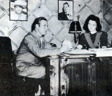 Gene dictates a letter to his secretary Dorothy Phillips. Note the pictures on the wall of Leo Carrillo and Rudy Vallee. Circa 1940.