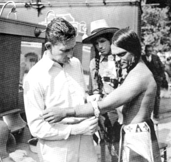 "Iron Eyes Cody watches as James Cagney is getting dressed as an Indian for ""Lady Killer"" ('33 Warner First-National). The basically non-Western film had gangster Cagney making it big in Hollywood before his old life caught up with him."