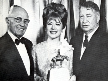 "Albert K. Mitchell, one-time president of the American Quarter Horse Association and Chill Wills stand beside Amanda Blake whose performance as Miss Kitty on ""Gunsmoke"" won her a Wrangler Award for Outstanding Fictional Television Program at the Cowboy Hall of Fame in 1966."