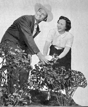 Gene Autry and his wife Ina examine a rose in the garden of their North Hollywood home in May, 1951.