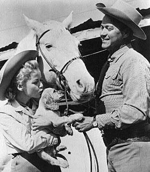 Gloria (Penny) Winters introduces her puppy to Kirby (Sky King) Grant and his horse.