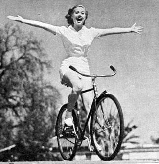 """Look Ma, no hands!"" Adele Mara shows off on her bike in March 1943."