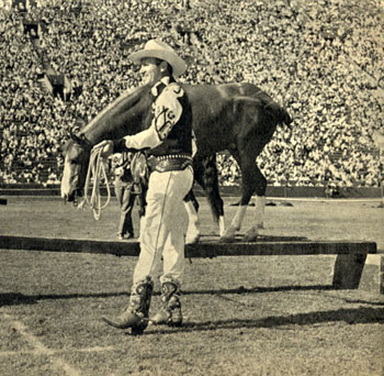 Gene Autry puts Little Champ (?) through his trick paces at the rodeo.