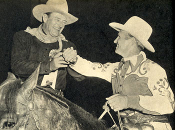 John Wayne obliges Gene Autry who needed a little help with his cuff button.