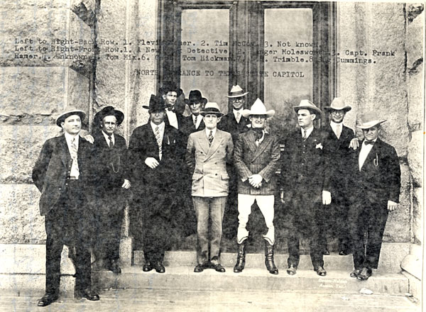 Tom Mix (front row third from right) stands in front of the north entrance to the Texas State Capitol with Texas Rangers (L-R back row) Flevis (illegible last name), man misidentified as Tim McCoy (unless that was the name of this Ranger), unknown Ranger. (L-R front row) illegible, Berger Moleswo???, Capt. Frank Hamer, unknown, Mix, Tom Hickman, L. E. Trimble, Sag Cummings.