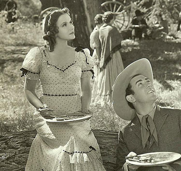 Pausing to look up at someone while eating lunch on location are Johnny Mack Brown and leading lady ???